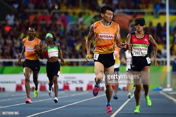Jin Zheng CHN and her guide Yubo Jin compete in the Women's 1500m - T11 Athletics Final at the Olympic Stadium during the Paralympic Games in Rio de...
