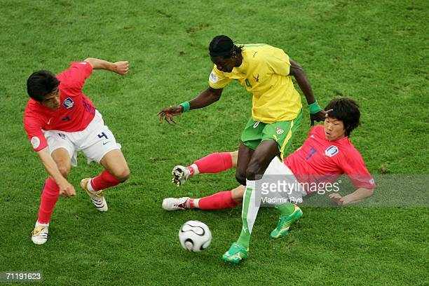 JinChul Choi and JiSung Park of South Korea battle with Emmanuel Adebayor of Togo for the ball during the FIFA World Cup Germany 2006 Group G match...