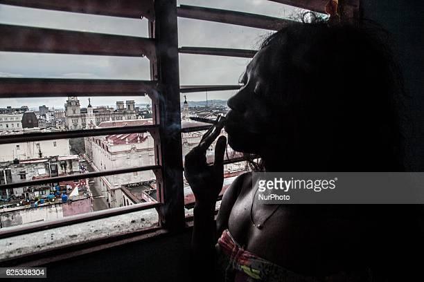 A jinetera in her rent room watching Havana