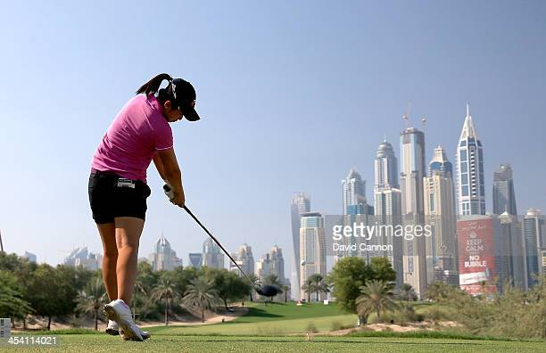 Jing Yan of China plays her tee shot at the par 4 8th hole during the final round of the 2013 Omega Dubai Ladies Masters on the Majilis Course at the...