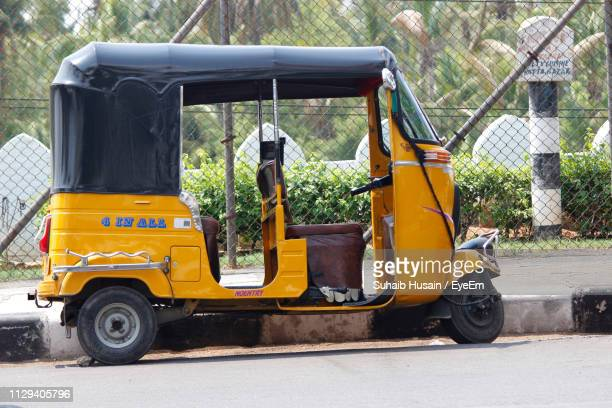 jinrikisha parked on street against fence - auto rickshaw stock pictures, royalty-free photos & images