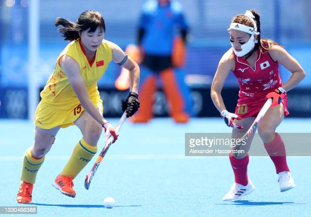Jinrong Zhang of Team China moves the ball past Hazuki Nagai of Team Japan during the Women's Pool B Match on day two of the Tokyo 2020 Olympic Games...