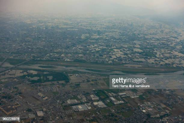Jintsu River and Toyama Airport in Japan daytime aerial view from airplane