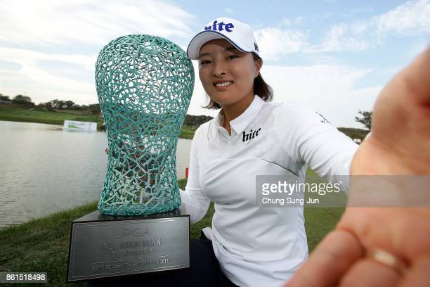 JinYoung Ko of South Korea imitates a selfie as she poses with the trophy during a ceremony following the LPGA KEB Hana Bank Championship at the Sky...