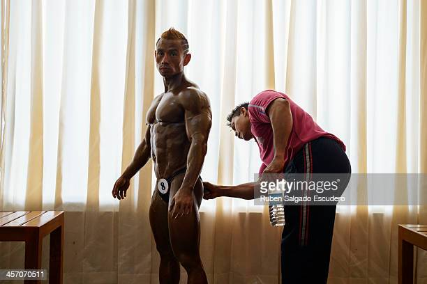 Jiraphan Pongkam of Thailand gets tanned up before competing in the 55kg category of the bodybuilding contest at the Myanmar Convention Center during...