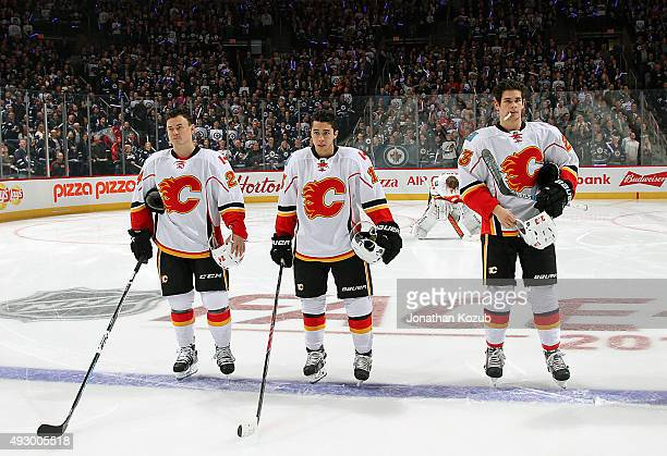 Jiri Hudler Johnny Gaudreau and Sean Monahan of the Calgary Flames stand on the blueline during the singing of 'O Canada' prior to NHL action against...