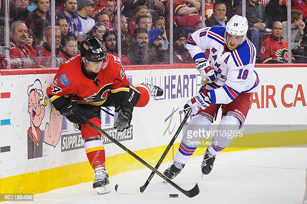 Jiri Hudler of the Calgary Flames battles Marc Staal of the New York Rangers for the puck during an NHL game at Scotiabank Saddledome on December 12...