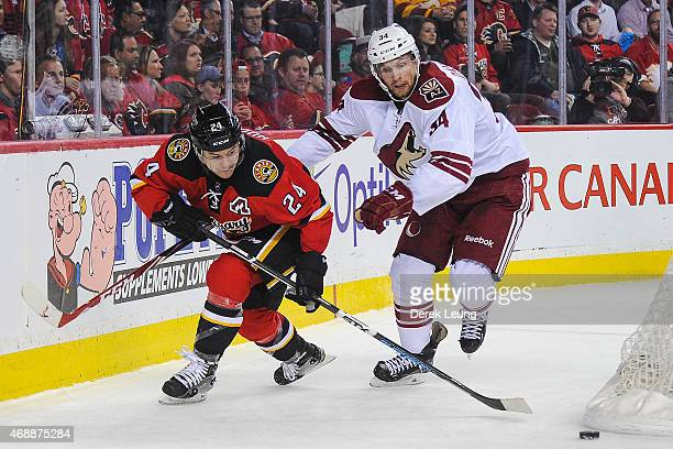 Jiri Hudler of the Calgary Flames chases the puck against Klas Dahlbeck of the Arizona Coyotes during an NHL game at Scotiabank Saddledome on April 7...