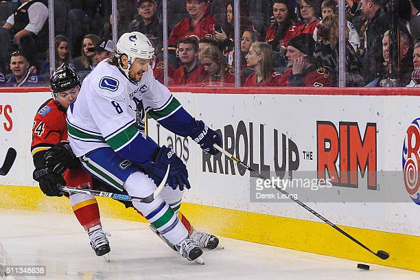 Jiri Hudler of the Calgary Flames fights Chris Tanev of the Vancouver Canucks for the puck during an NHL game at Scotiabank Saddledome on February 19...