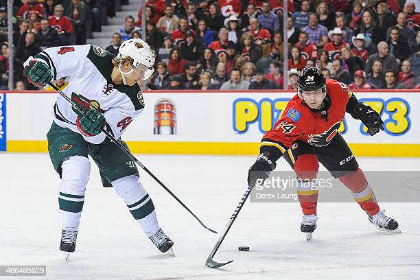 Jiri Hudler of the Calgary Flames fights for the puck against Mikael Granlund of the Minnesota Wild during an NHL game at Scotiabank Saddledome on...