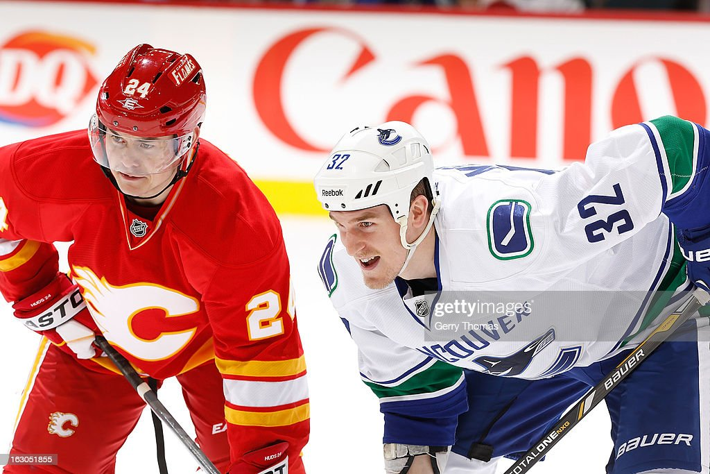Jiri Hudler #24 of the Calgary Flames in a faceoff against Dale Weise #32 of the Vancouver Canucks on March 3, 2013 at the Scotiabank Saddledome in Calgary, Alberta, Canada.