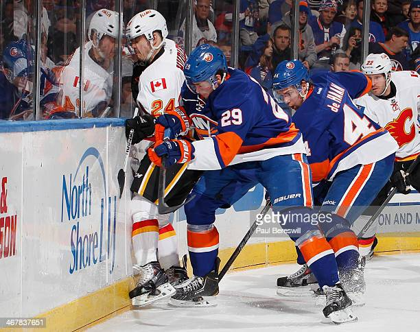 Jiri Hudler of the Calgary Flames is checked into the boards by Brock Nelson of the New York Islanders in an NHL hockey game at Nassau Veterans...