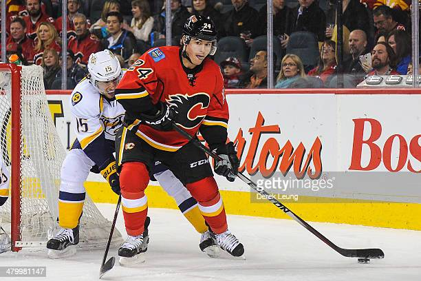 Jiri Hudler of the Calgary Flames skates with the puck against Craig Smith of the Nashville Predators during an NHL game at Scotiabank Saddledome on...