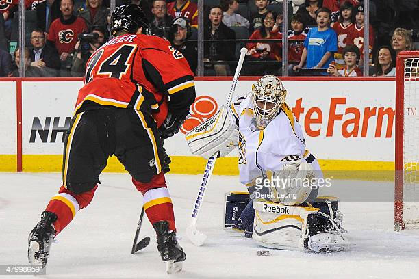 Jiri Hudler of the Calgary Flames takes a shot on Carter Hutton of the Nashville Predators during an NHL game at Scotiabank Saddledome on March 21...