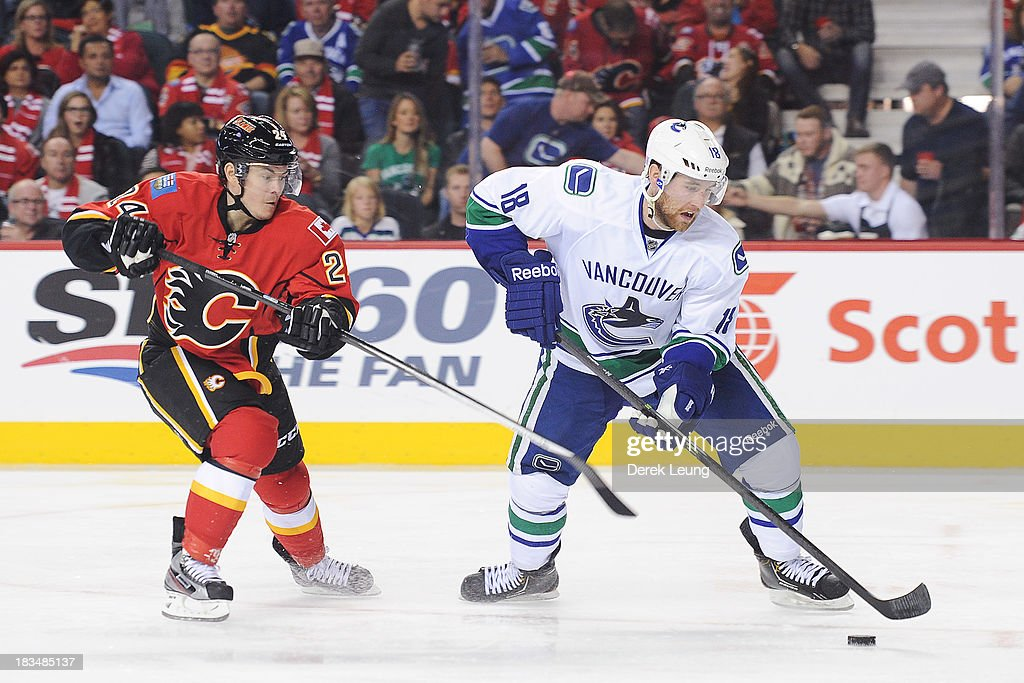 Jiri Hudler #24 of the Calgary Flames tries to steal the puck from Ryan Stanton #18 of the Vancouver Canucks during the Flames' home opening NHL game at Scotiabank Saddledome on October 6, 2013 in Calgary, Alberta, Canada. The Vancouver Canucks won 5-4 in OT.