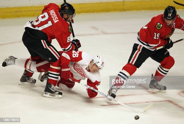 Jiri Hudler of the Detroit Red Wings pokes at the puck as he is dropped by Marian Hossa of the Chicago Blackhawks as Jonathan Toews keeps his eyes on...
