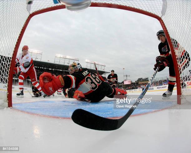 Jiri Hudler of the Detroit Red Wings scores his second goal while goalie Cristobal Huet and Duncan Keith of the Chicago Blackhawks try to stop him...