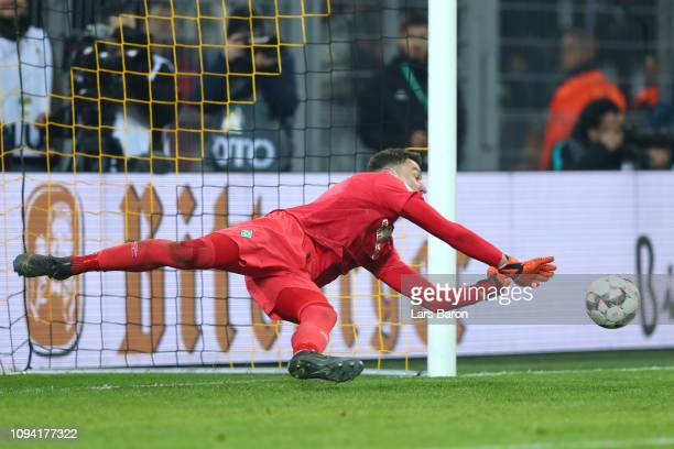 Jiri Pavlenka of Werder Bremen saves a penalty from Paco Alcacer of Borussia Dortmund in the penalty shoot out during the DFB Cup match between...