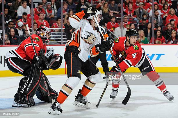 Jiri Sekac of the Anaheim Ducks and Niklas Hjalmarsson of the Chicago Blackhawks wait in position in front of goalie Corey Crawford in the first...