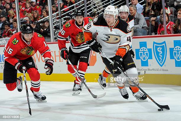 Jiri Sekac of the Anaheim Ducks takes control of the puck ahead of Artem Anisimov and Teuvo Teravainen of the Chicago Blackhawks in the second period...