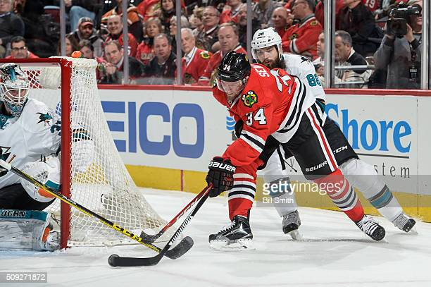Jiri Sekac of the Chicago Blackhawks attempts to score on goalie Martin Jones of the San Jose Sharks as Brent Burns follows in the first period of...