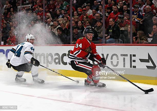 Jiri Sekac of the Chicago Blackhawks turns to pass under pressure from MarcEdouard Vlasic of the San Jose Sharks at the United Center on February 9...