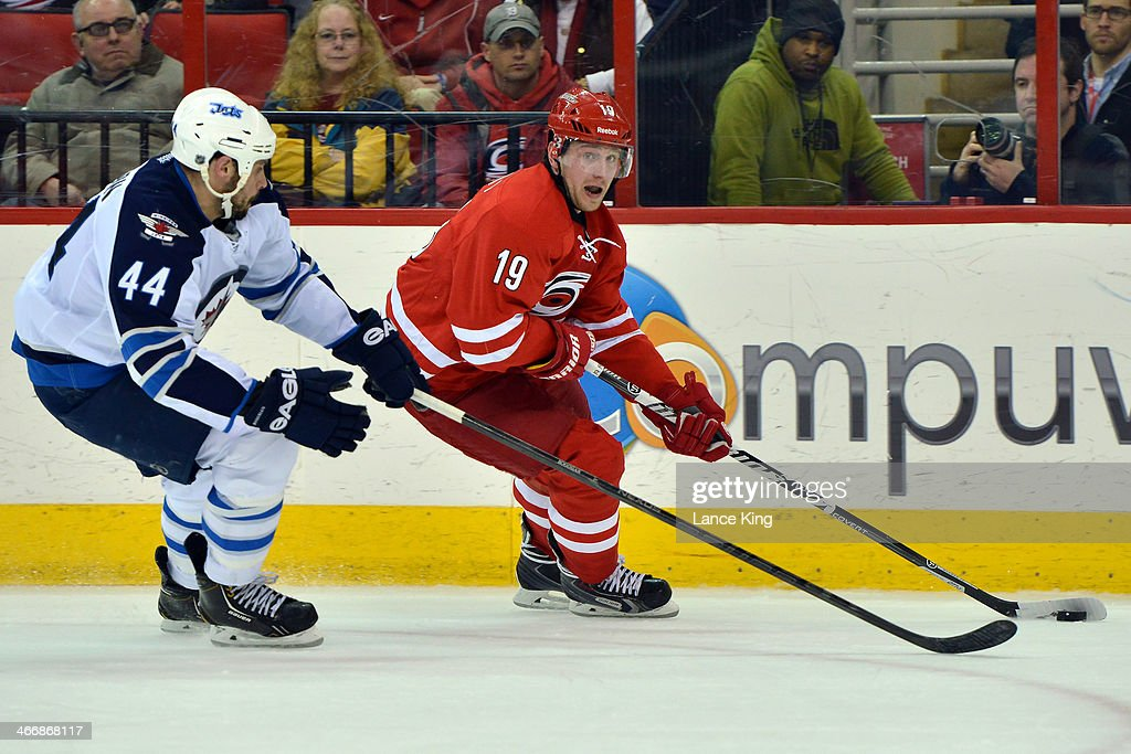 Jiri Tlusty #19 of the Carolina Hurricanes skates with the puck against Zach Bogosian #44 of the Winnipeg Jets at PNC Arena on February 4, 2013 in Raleigh, North Carolina. The Jets defeated the Hurricanes 2-1.