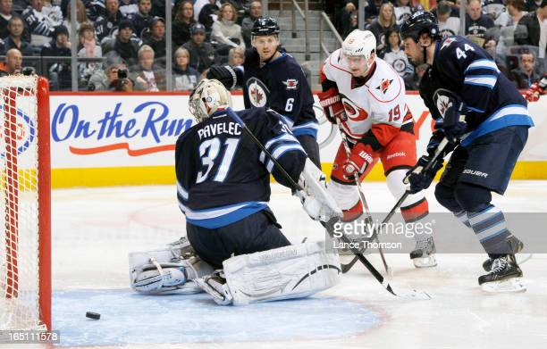 Jiri Tlusty of the Carolina Hurricanes stands between Ron Hainsey and Zach Bogosian of the Winnipeg Jets as they watch the puck slide behind...