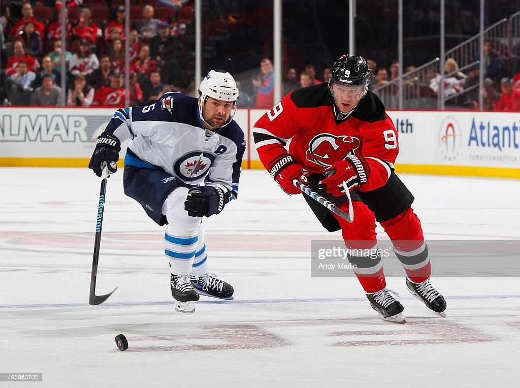 Jiri Tlusty #9 of the New Jersey Devils and Mark Stuart #5 of the Winnipeg Jets pursue a loose puck during the game at the Prudential Center on October 9, 2015 in Newark, New Jersey.The Jets defeated the Devils 3-1.