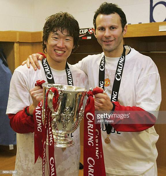 JiSung Park and Ryan Giggs of Manchester United pose with the Carling Cup trophy in the dressing room after the Carling Cup Final match between...