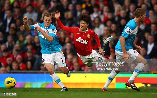 JiSung Park of Man Utd is brought down by Sebastien Larsson and Michael Turner of Sunderland during the Barclays Premier League match between...