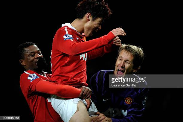 JiSung Park of Manchester United celebrates scoring the winning goal with team mates Patrice Evra and Edwin van der Sar during the Barclays Premier...