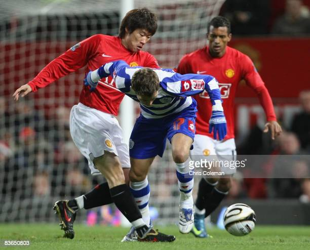 JiSung Park of Manchester United clashes with Lee Cook of Queens Park Rangers during the Carling Cup Fourth Round match between Manchester United and...
