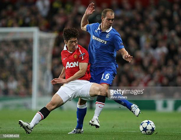 JiSung Park of Manchester United clashes with Steven Whittaker of Glasgow Rangers during the UEFA Champions League Group C match between Manchester...