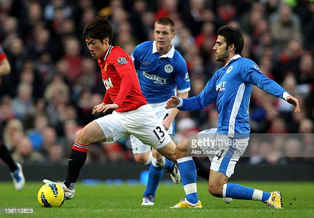 JiSung Park of Manchester United competes with Jordi Gomez of Wigan Athletic during the Barclays Premier League match between Manchester United and...