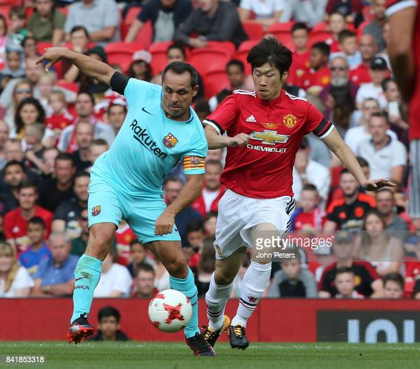 JiSung Park of Manchester United Legends in action with Sergi Barjuan of Barcelona Legends during the MU Foundation charity match between Manchester...