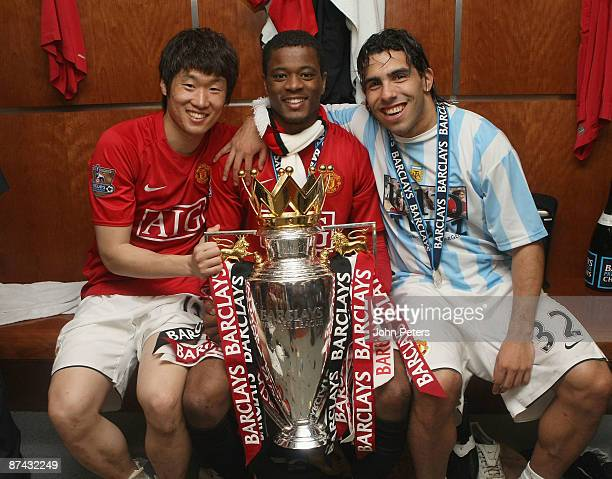 JiSung Park Patrice Evra and Carlos Tevez of Manchester United celebrate with the Premier League trophy in the dressing room after the Barclays...
