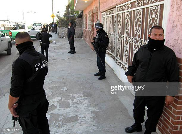 Jittery cops stand guard along a street in Ciudad Juarez December 8 shortly after crime gang commandos ambushed a police vehicle killing three cops
