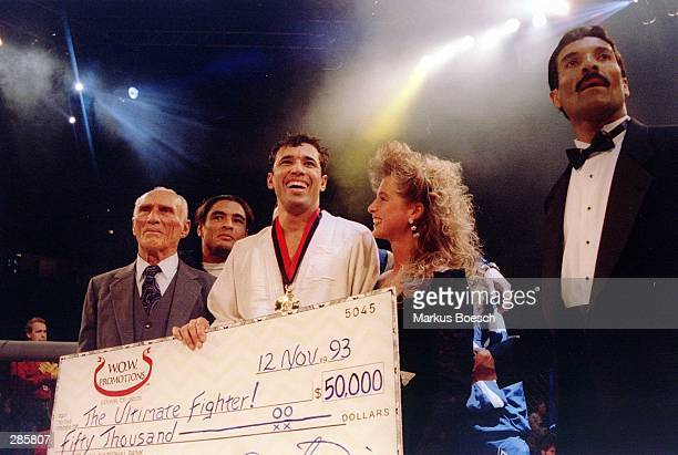 """Jiu-Jitsu black belt Royce Gracie receives a $50,000 check after becoming """"The Ultimate Fighter"""" by defeating Gerard Gordeau of the Netherlands int..."""