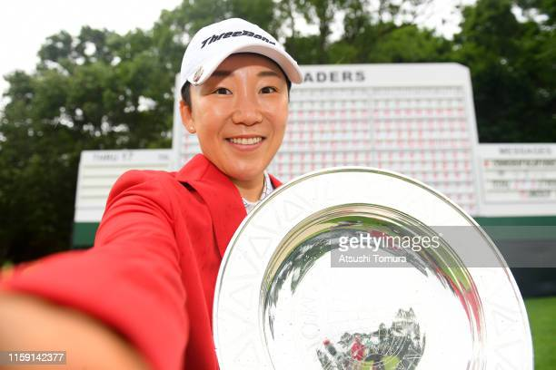 Jiyai Shin of South Korea imitates a selfie with the trophy after the award ceremony following the final round of the Earth Mondamin Cup at the...