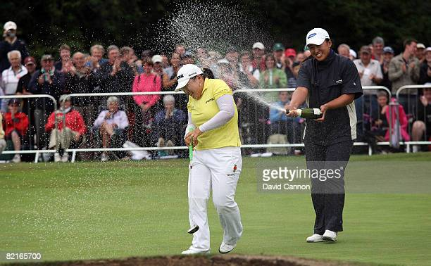 JiYai Shin of South Korea is sprayed with champagne on the 18th green after holing the winning putt by fellow Korean golfer Amy Yang during the final...