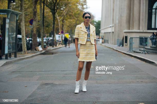 Jiyoung Kim wears black sunglasses a yellow shortsleeve Chanel tweed suit jacket and skirt Iron Maiden tshirt white boots before the Miu Miu show...
