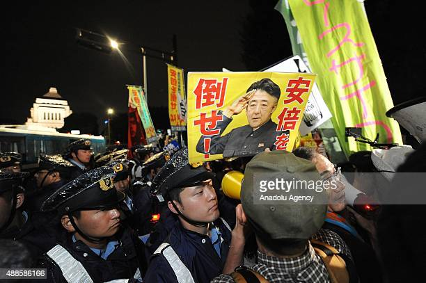 JJapanese police officers stand guard as protesters stage a rally against Japan Security Bills in front of the National Diet building in Tokyo Japan...