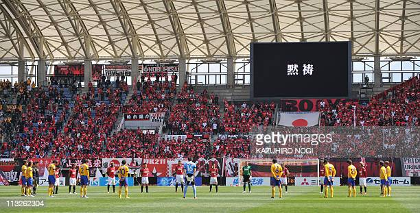 JLeague football players of Vegalta Sendai and Urawa Reds offer a silent prayer for the victims of the March 11 earthquake and tsunami prior to their...