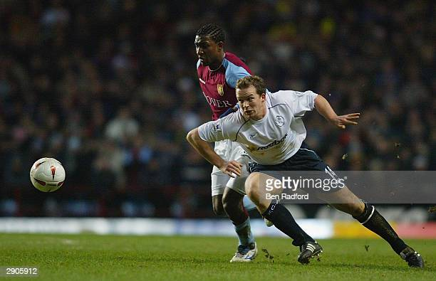 Jlloyd Samuel of Aston Villa is tackled by Kevin Davies of Bolton Wanderers during the Carling Cup second leg semi final match between Aston Villa...