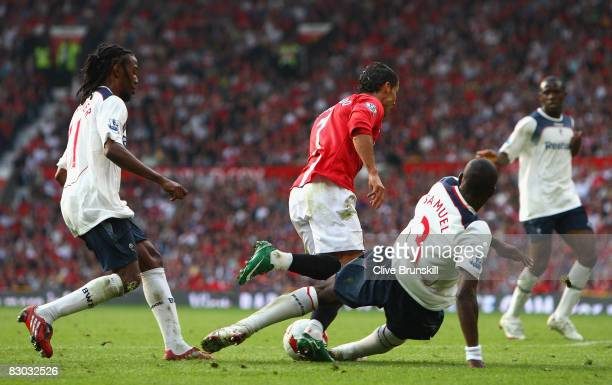 Jlloyd Samuel of Bolton Wanderers brings down Cristiano Ronaldo of Manchester United to concede a penalty kick during the Barclays Premier League...