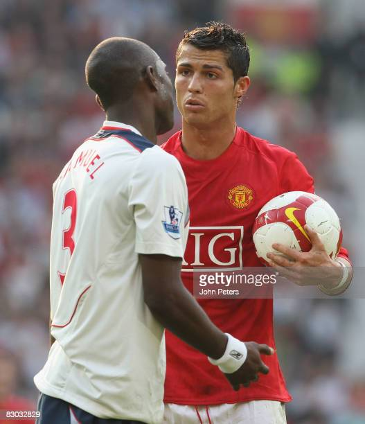 Jlloyd Samuel of Bolton Wanderers complains to Cristiano Ronaldo of Manchester United after Ronaldo won a penalty during the FA Premier League match...