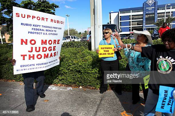 Jo Ann Harris Betty Ferguson and Dorothy Smith try to speak with a supporter of keeping Judge Thomas off the federal bench as they protest on the...