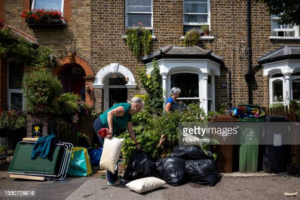 Jo Danischewsky moves water-damaged pillows and bags of belongings on the pavement outside her daughter Sonia Danischewsky's home on Wadley Road in...