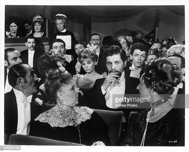 Jo Dassin tries to attract the attention of a colleague seated two rows in front of him at a piano recital in a scene from the film 'Lady L' 1965